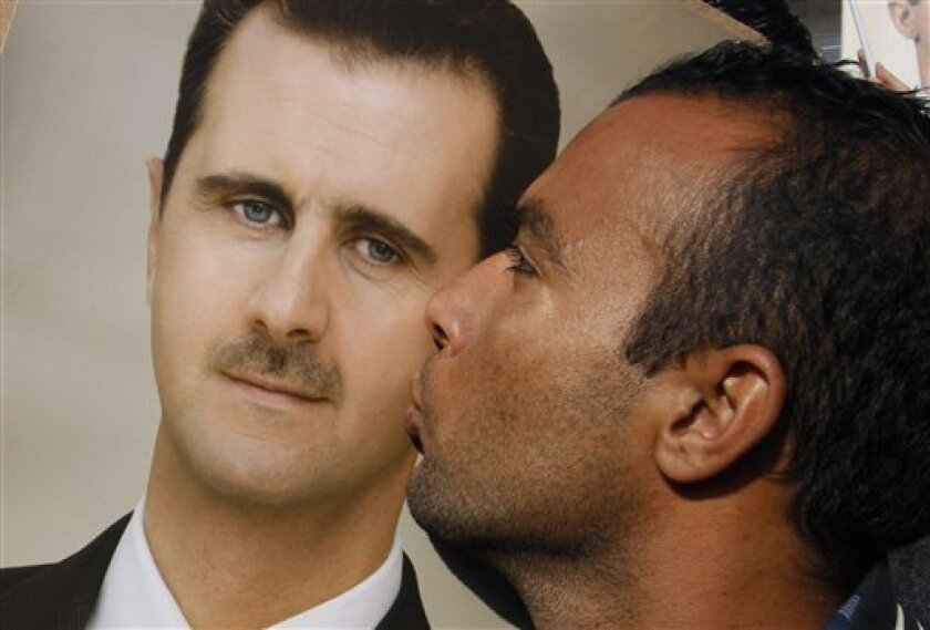A pro-Syrian regime protester kisses a portrait of Syrian President Bashar Assad during a demonstration in support of their President, in Damascus, Syria, on Wednesday Jan. 4, 2012. Activists accused President Bashar Assad's regime on Wednesday of misleading Arab League observers by taking them only to areas loyal to the government and changing street signs to confuse them. (AP Photo/Muzaffar Salman)