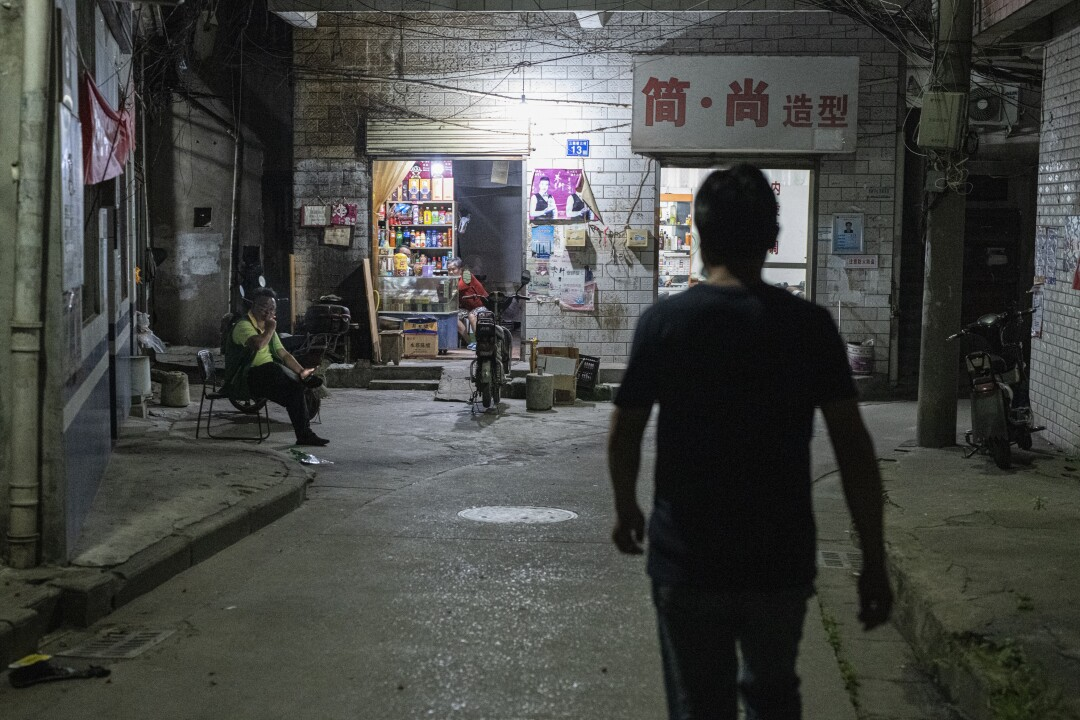 Wang Guoqing, a migrant worker in Wuhan, walks toward his rented home