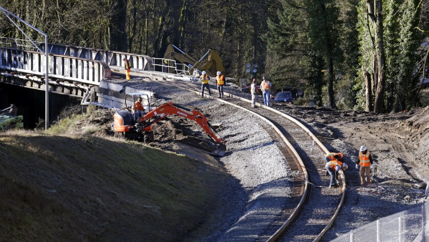 A crew works Wednesday on the curved stretch of track leading to the bridge in Washington state where an Amtrak train derailed two days earlier