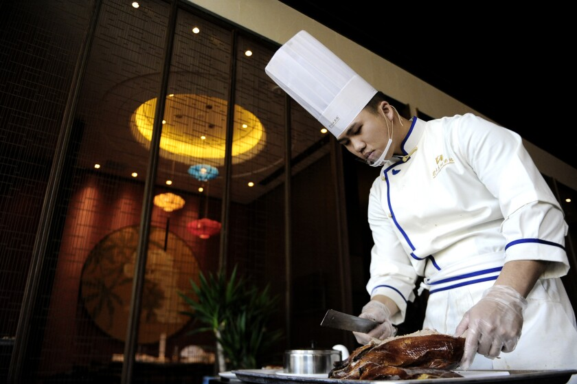 Chef Ted Yang carves the Meizhou duck at Dongpo restaurant.