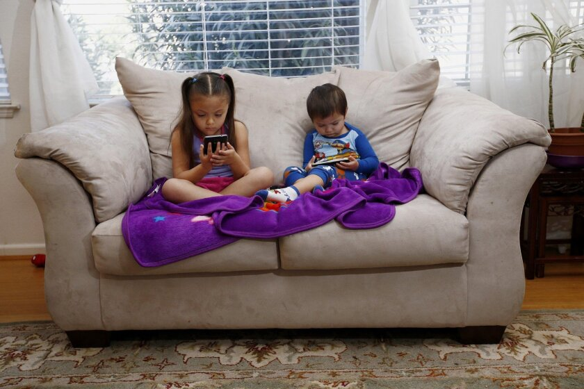 Juliana Sanchez, 5, and her brother, Francisco Sanchez Jr., 2, watch children's programming on YouTube on their parent's cell phones at their home on Monday, March 9, 2015 in Mountain House, Calif. Watching digital video on hand-held devices is the new normal for tots, tweens and teens.