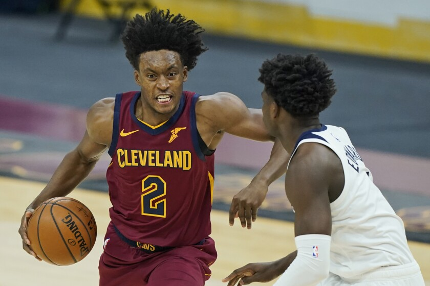 Cleveland Cavaliers' Collin Sexton, left, drives against Minnesota Timberwolves' Anthony Edwards in the first half of an NBA basketball game, Monday, Feb. 1, 2021, in Cleveland. (AP Photo/Tony Dejak)