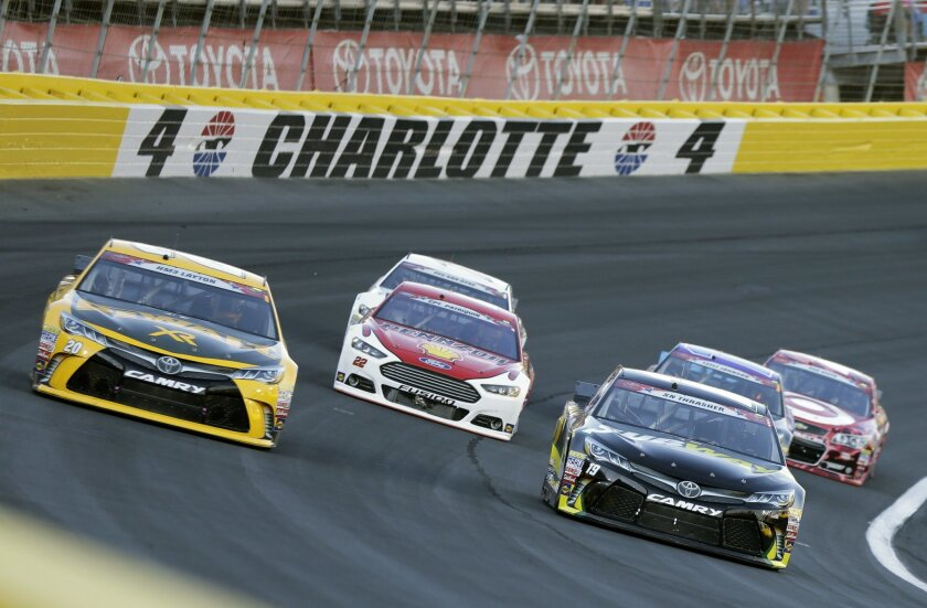 Matt Kenseth (20) and Carl Edwards (19) race out of Turn 4 during the NASCAR Sprint Cup series auto race at Charlotte Motor Speedway in Concord, N.C., Sunday, May 24, 2015. (AP Photo/Chuck Burton)