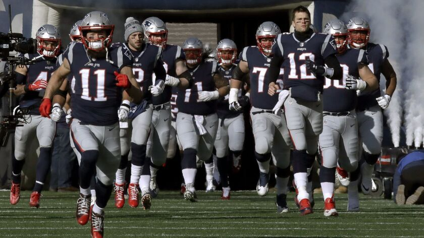 New England Patriots wide receiver Julian Edelman (11) and quarterback Tom Brady (12) lead their team onto the field before an NFL divisional playoff game against the Chargers in Foxborough, Mass. on Sunday.