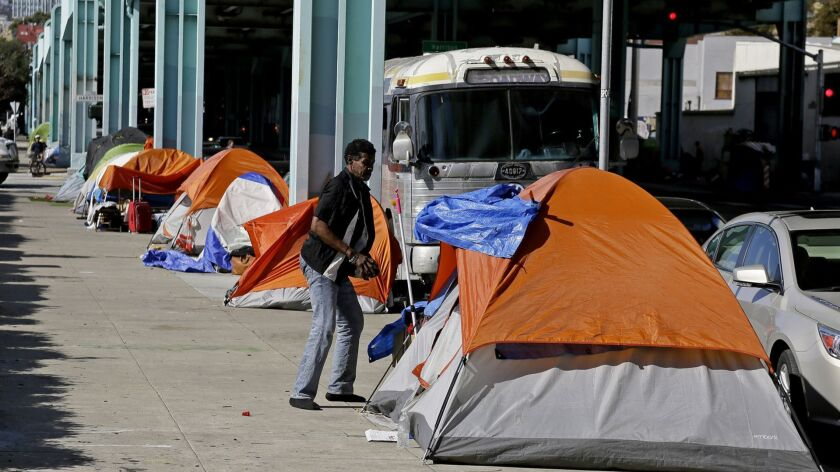 FILE - In this Feb. 23, 2016 file photo, a man stands outside his tent on Division Street in San Fra