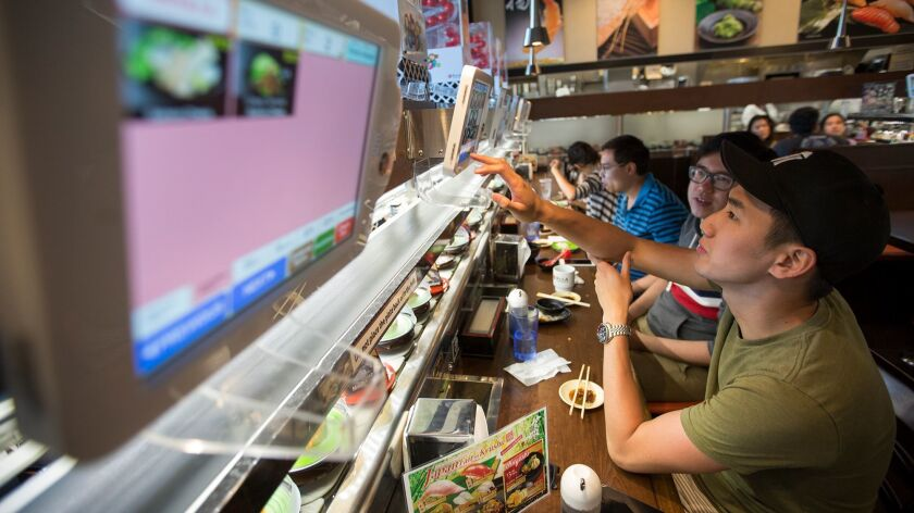Thai Phi and Kenny Cheng from Toronto select their food from an electronic menu at the Kula Revolving Sushi Bar restaurant at Diamond Jamboree.