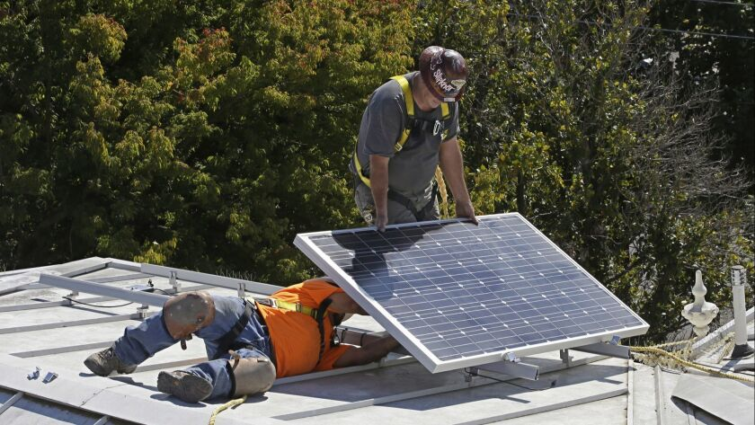 FILE-- In this Oct. 16, 2015 file photo a solar panel is installed on the roof of the Old Governor's