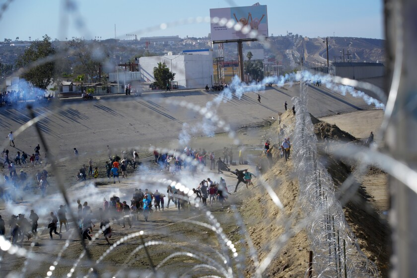 Border Patrol agents use tear gas on migrants Sunday at the U.S.-Mexico border fence near the San Ysido Port of Entry.