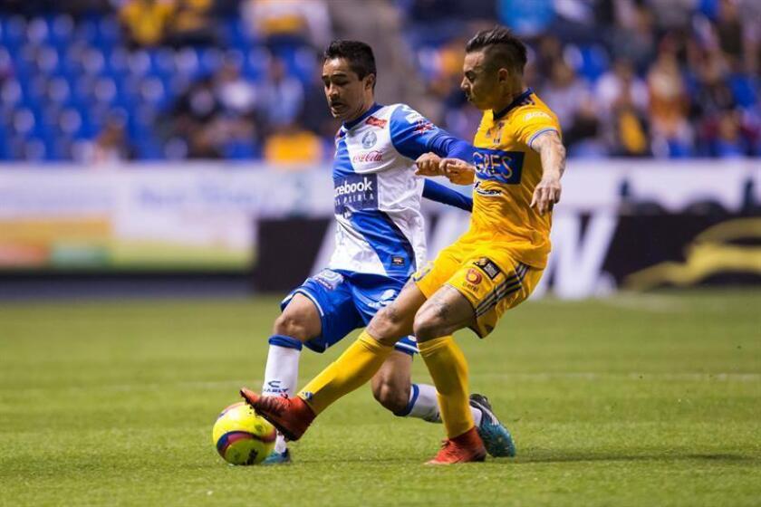 El jugador de Puebla Alonso Zamora (i) y Eduardo vargas (d) de Tigres pelean por el balón hoy, viernes 5 de enero de 2018, durante el juego correspondiente a la jornada 1 del torneo mexicano de fútbol, disputado en el estadio Cuauhtémoc en la ciudad de Puebla (México). EFE