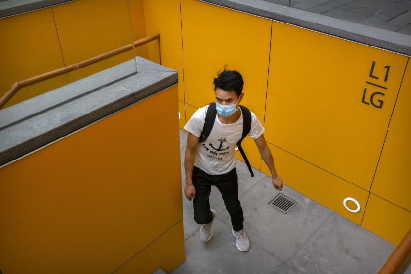 A man wearing a face mask to protect against the coronavirus walks up a staircase at an outdoor shopping area in Beijing, Saturday, Aug. 1, 2020. China reported a more than 50% drop in new cases of COVID-19 on Saturday in a possible sign that its latest major outbreak in the northwestern region of Xinjiang may be waning. (AP Photo/Mark Schiefelbein)