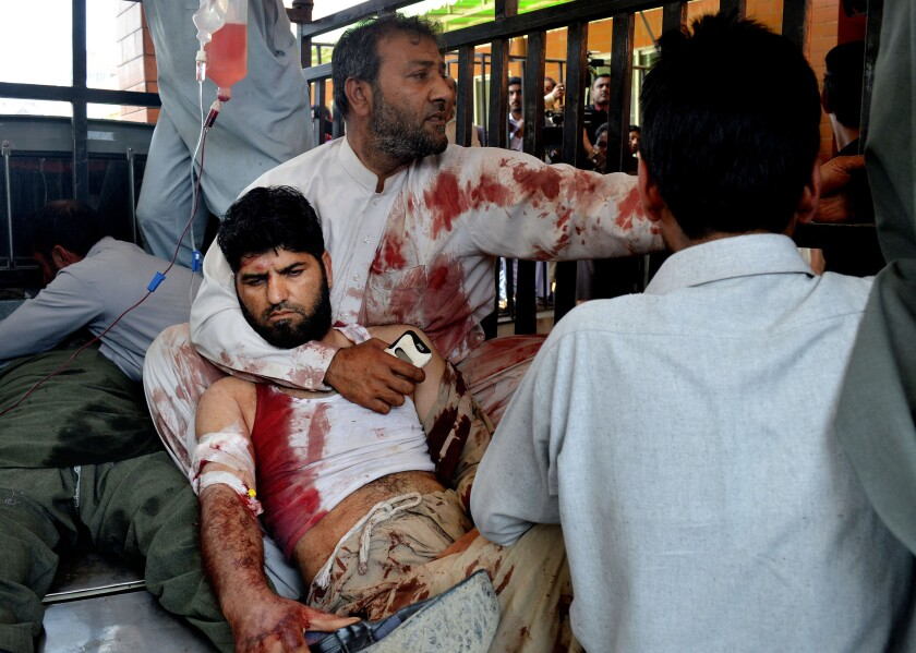 Volunteers carry an injured man to a hospital in Peshawar, Pakistan, on March 7 after a suicide bomber attacked a nearby court complex.