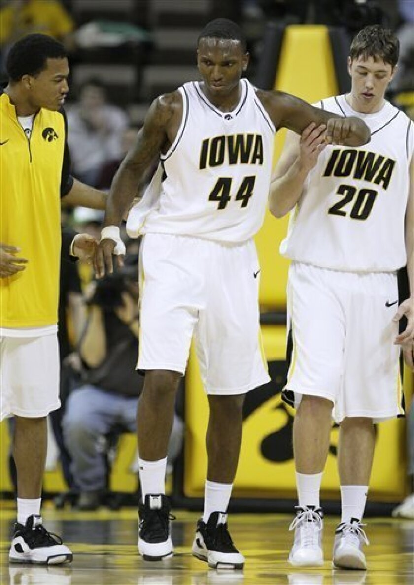 Iowa's Cyrus Tate (44) limps off the court with teammates Jarryd Cole, left, and Andrew Brommer, right, after an injury during the first half of an NCAA college basketball game against Minnesota, Thursday, Jan. 8, 2009, in Iowa City, Iowa. (AP Photo/Charlie Neibergall)