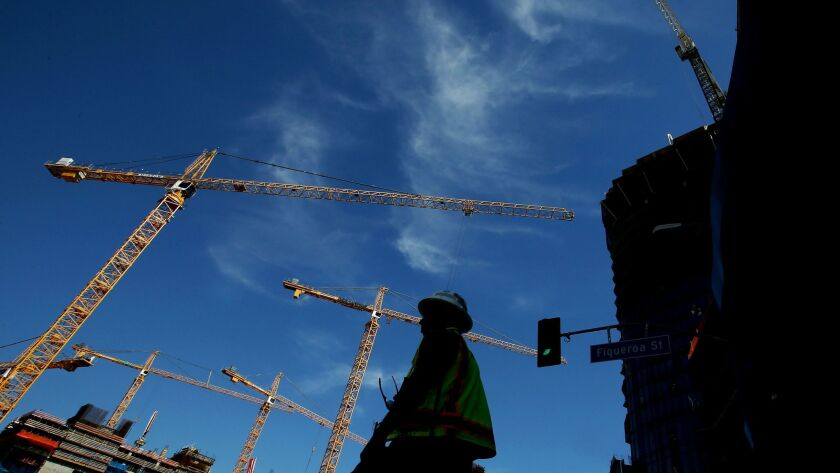Construction cranes loom over a development site along Figueroa Street near the L.A. Live entertainment and hotel complex in downtown Los Angeles.