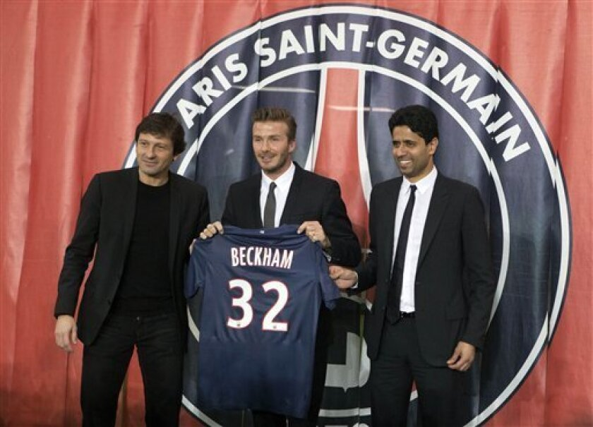 Sports Director Leonardo, left, British soccer player David Beckham, center, and Paris Saint Germain's President Nasser Al-Khelaifi, right, pose with Backham's jersey during a press conference, in at the Parc des Princes stadium in Paris, Thursday, Jan. 31, 2013. David Beckham will join Paris Saint-Germain on Thursday, opting for a move to France after mulling over lucrative offers from around the world since leaving the Los Angeles Galaxy.(AP Photo/Michel Euler)