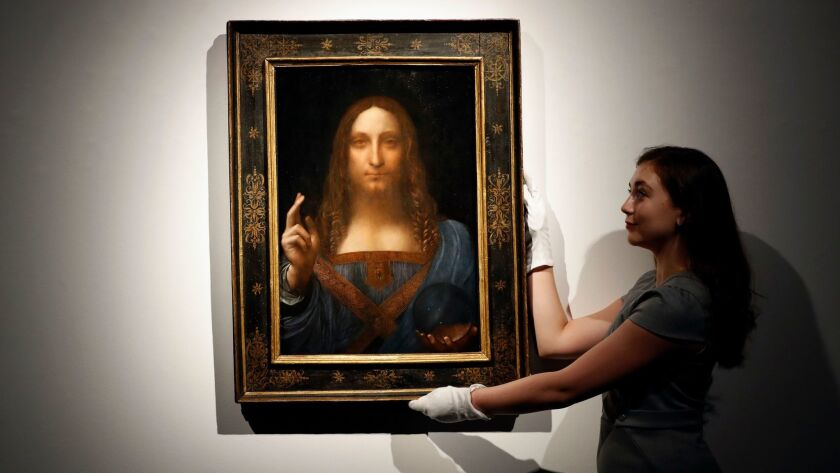 "FILE- In this Oct. 24, 2017 file photo, an employee poses with Leonardo da Vinci's ""Salvator Mundi"""