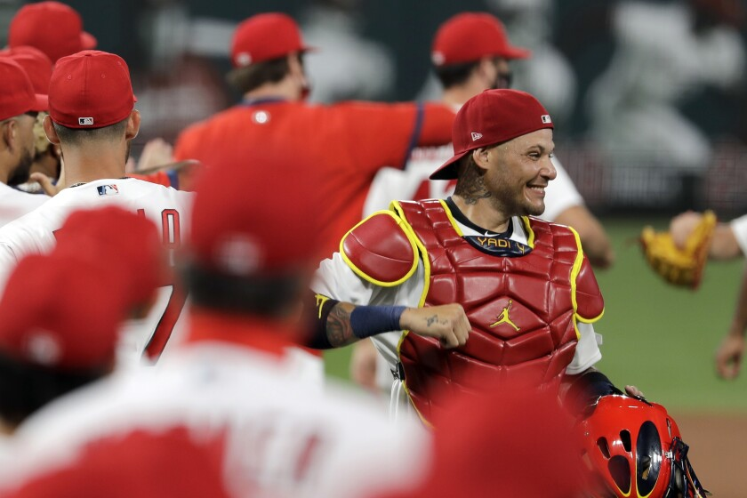 FILE - In this Friday, July 24, 2020, file photo, St. Louis Cardinals catcher Yadier Molina, right, celebrates a 5-4 win over the Pittsburgh Pirates in a baseball game in St. Louis. Molina says he's one of the players on his team who has tested positive for the coronavirus. The nine-time All-Star revealed his diagnosis Tuesday, Aug. 4, 2020, in a Spanish-language Instagram post. (AP Photo/Jeff Roberson, File)
