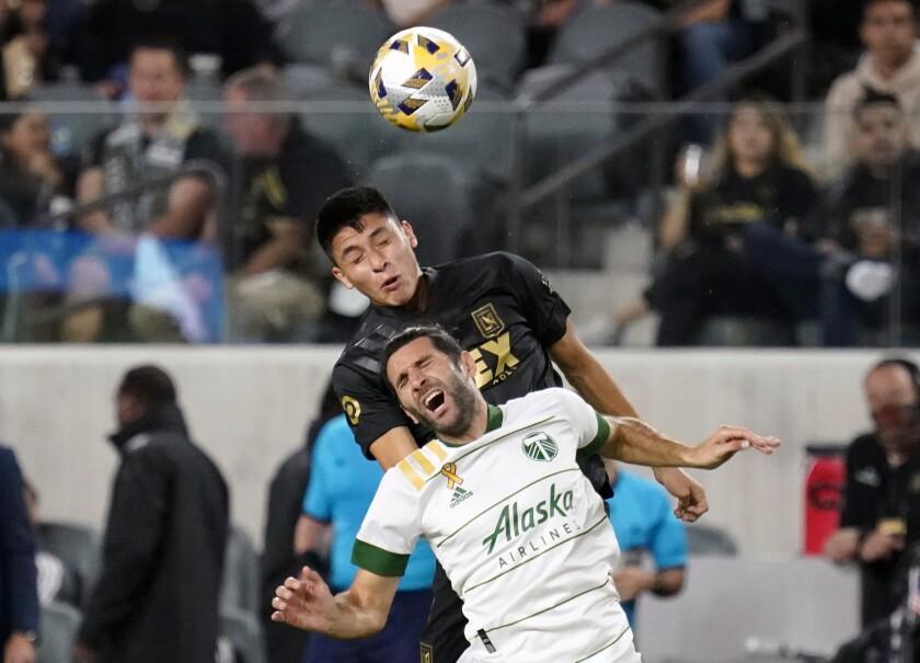 Portland Timbers midfielder Diego Valeri is defended by LAFC defender Marco Farfan.