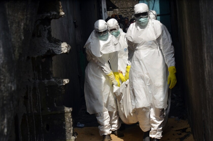 Red Cross workers carry the body of a person who died from Ebola in Monrovia earlier this month.