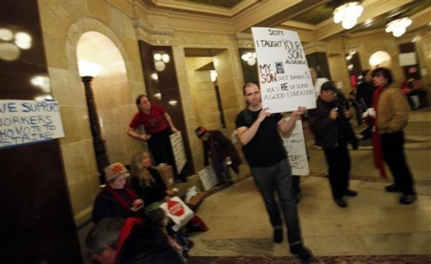 Teacher Michael Mulvey of West Allis, Wis., carries a sign in the rotunda at the State Capitol in Madison, Wis., Sunday, Feb. 20, 2011. Opponents to the governor's bill to eliminate collective bargaining rights for many state workers are on their sixth day of protesting. (AP Photo/Andy Manis)