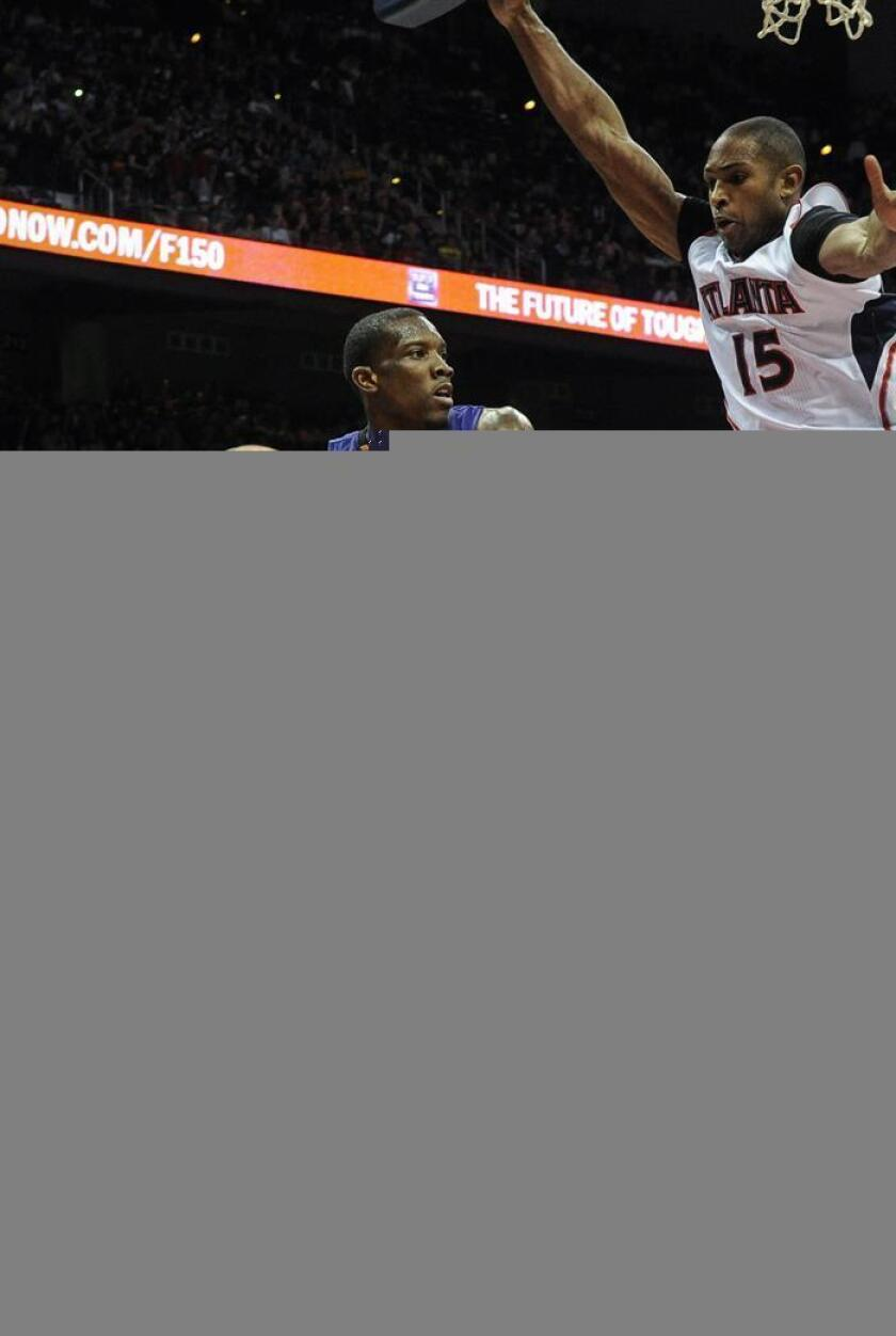 El jugador de Suns Eric Bledsoe (i) pasa el balón ante la marca de Al Horford (d), de Hawks, durante un partido por la NBA. EFE/Archivo