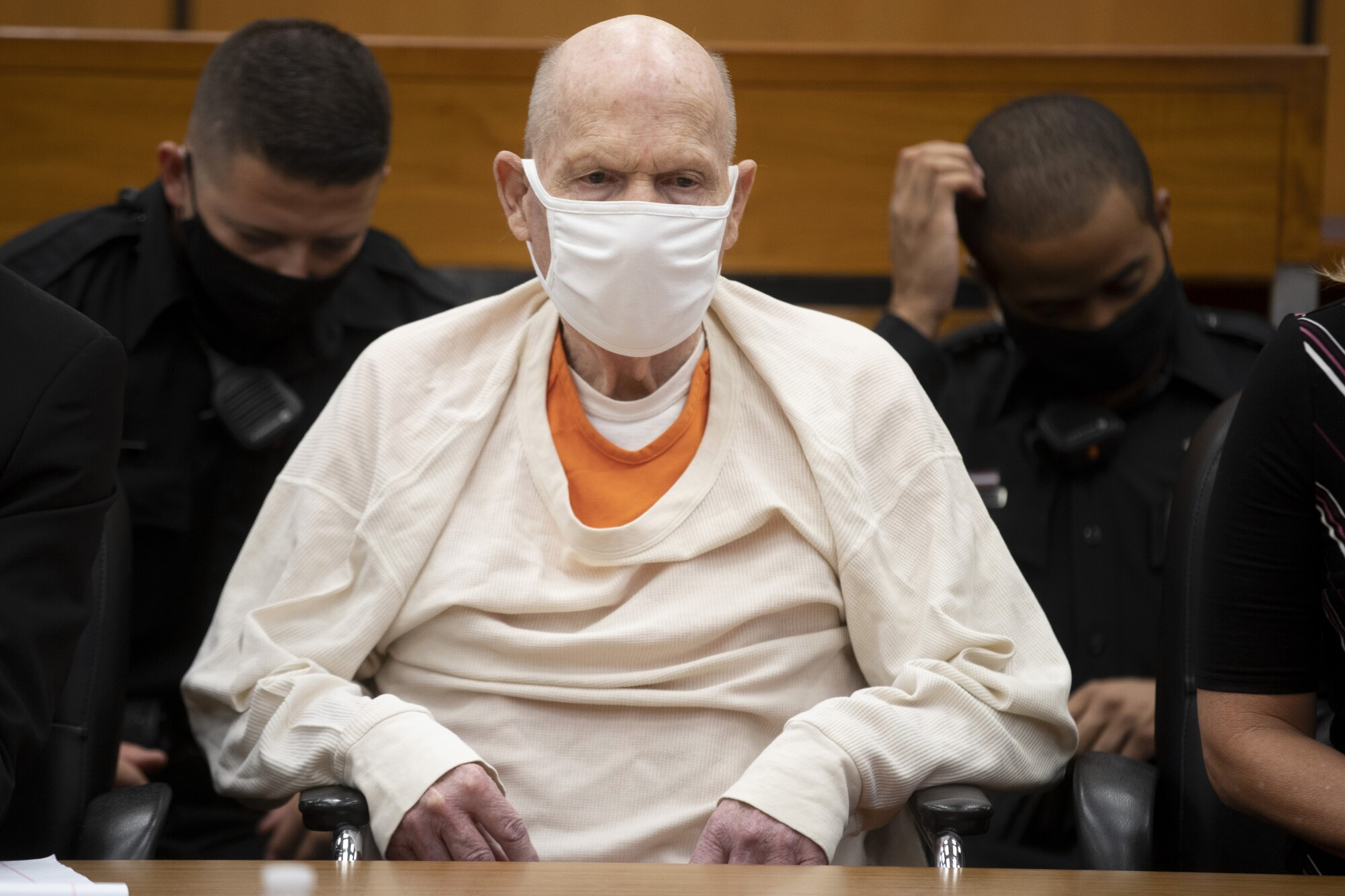 A masked Joseph James DeAngelo Jr. sits in a courtroom