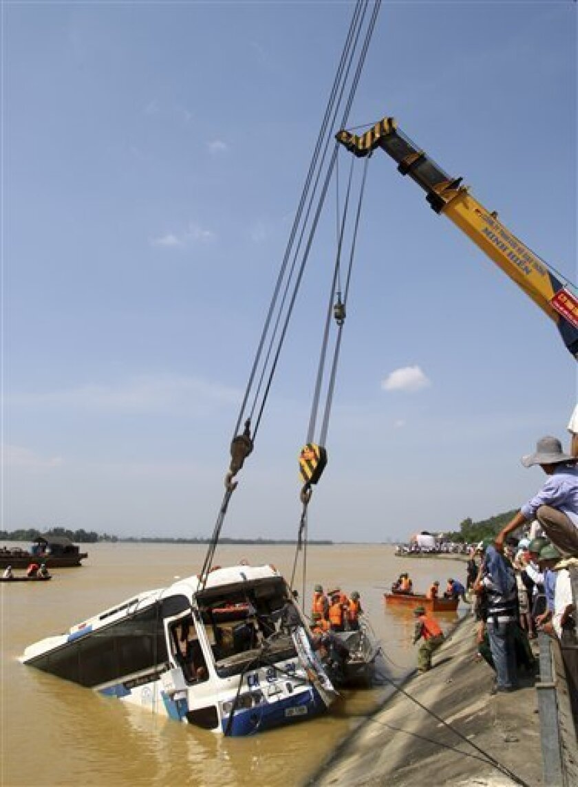 The bus which was swept away off a road early Monday morning by high waters, is pulled out of water by two cranes in Nghi Xuan, Ha Tinh, central Vietnam, Thursday, Oct. 21, 2010.  Rescuers pulled nine bodies, including those of three children, from the bus winched off a river bottom and dragged to