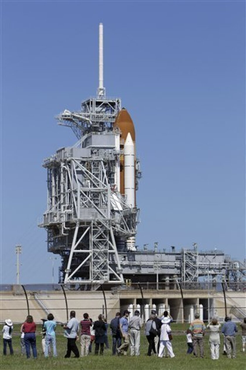 Visitors at the Kennedy Space Center take photos and get a close view of space shuttle Endeavour on Pad 39A in Cape Canaveral, Fla., Saturday, April 30, 2011. Yesterdays' launch attempt was scrubbed due to technical problems.(AP Photo/John Raoux)