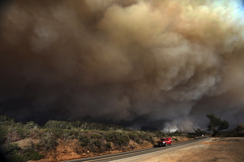A massive column of smoke rises above Highway 1 just north of the Santa Cruz County line as a section of the CZU August Lightning Complex burns above Waddell Beach, Wednesday Aug. 19, 2020, northwest of Santa Cruz, Calif. (Shmuel Thaler/The Santa Cruz Sentinel via AP)