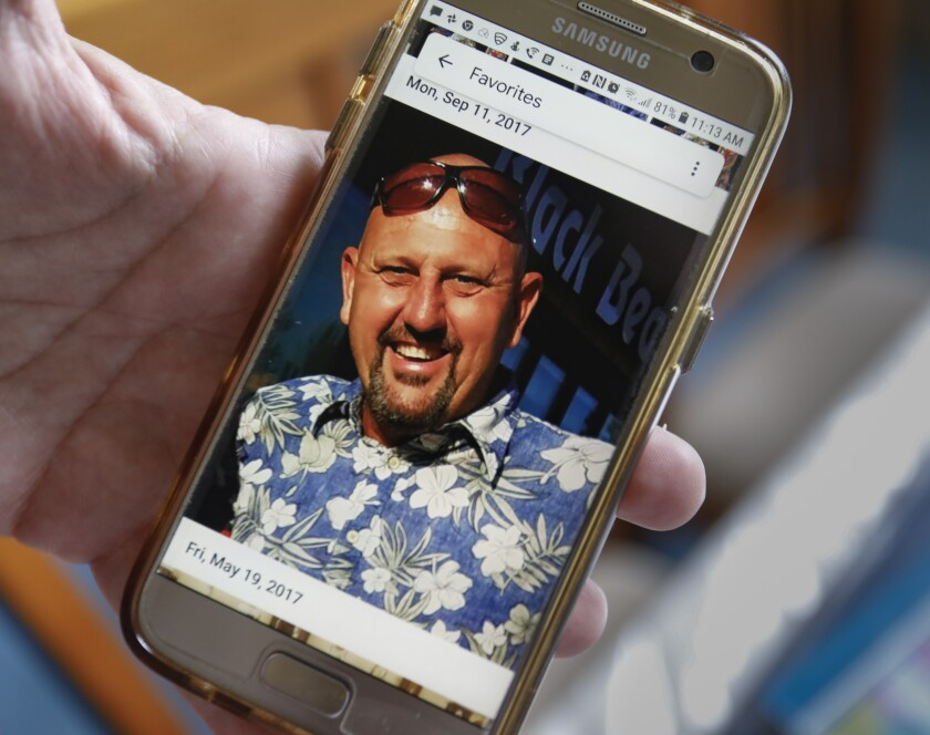 HeadTheresa Sturkie  holds a cell phone with a photo of her husband of 21 years, John Sturkie,  at her home on May 21, 2019 in Oceanside, California.line