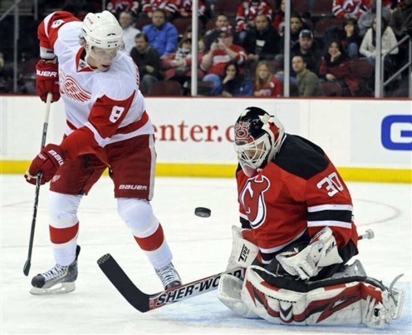 New Jersey Devils goaltender Martin Brodeur, right, makes a save as Detroit Red Wings' Justin Abdelkader looks for a rebound during the first period of an NHL hockey game Saturday, Dec. 5, 2009 in Newark, N.J. (AP Photo/Bill Kostroun)