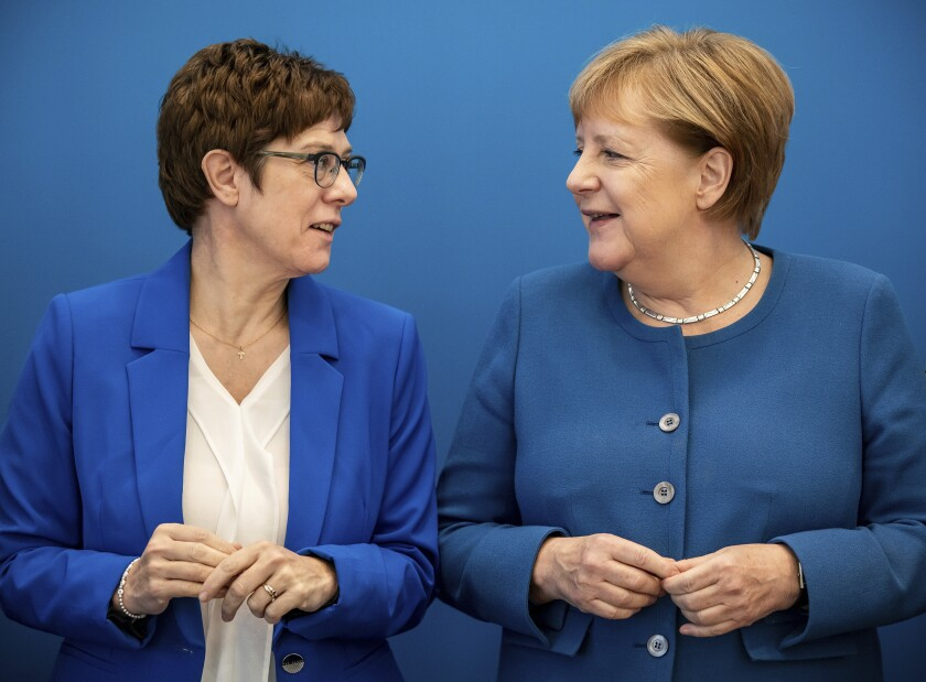 Annegret Kramp-Karrenbauer, left, CDU Federal Chairman and Defence Minister, stands next to Chancellor Angela Merkel (CDU) at the beginning of the meeting of the CDU Federal Executive Committee in the Konrad-Adenauer-Haus in Berlin, German, Monda, Dec.9, 2019. (Michael Kappeler/dpa via AP)