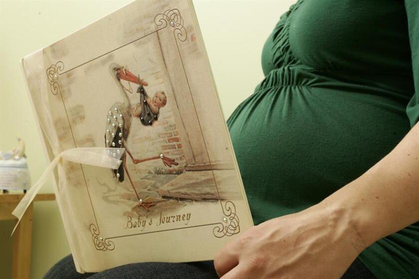 Una mujer en su noveno mes de embarazo mira un álbum de fotos. EFE/Archivo