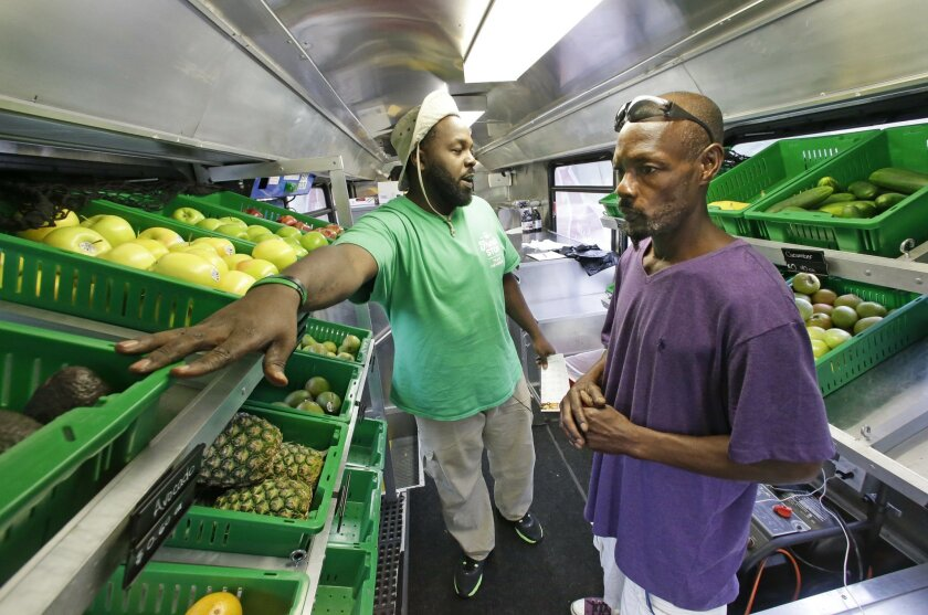 In this Wednesday, July 15, 2015 photo, Fresh Stop employee Jamar Allen, left, helps Jock Riggins as he shops on the Fresh Stop bus, a mobile market, in Eatonville, Fla. The Fresh Stop brings fresh fruits and vegetables to communities with no supermarkets. The nation's largest grocery chains have built new supermarkets in only a fraction of the neighborhoods where they're needed most, according to an analysis of federal food stamp data by The Associated Press. (AP Photo/John Raoux)