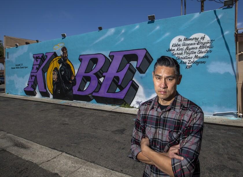 Artist Tyke Witnes stands in front of his Kobe mural at El Toro Bravo Tortilleria in Costa Mesa.
