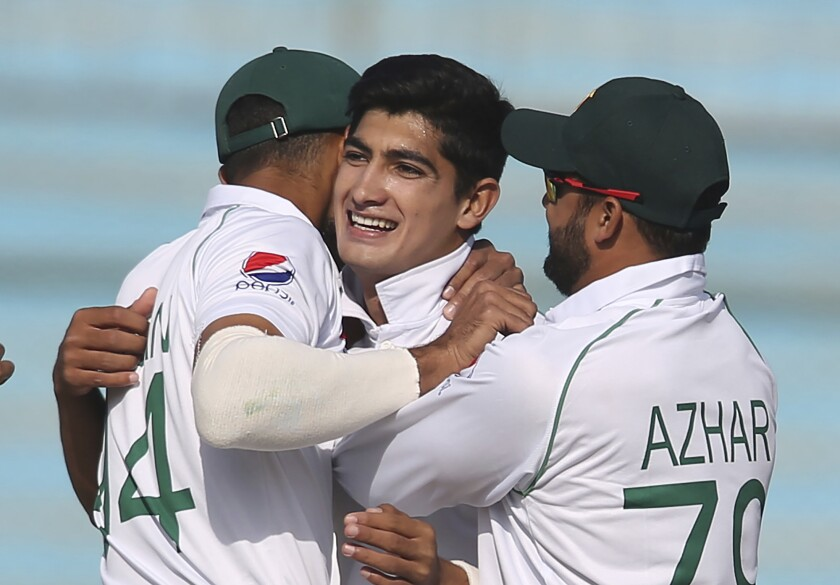 Pakistani captain Azhar Ali and teammate greet young Pakistani bowler Naseem Shah, center, for taking wicket of Sri Lankan batsman during the Test in Karachi, Pakistan, Monday, Dec. 23, 2019. Teenager Shah became the youngest fast bowler to take a five-wicket haul in test cricket history as Pakistan completed a winning comeback to tests on home soil with a 1-0 series victory over Sri Lanka on Monday. (AP Photo/Fareed Khan)