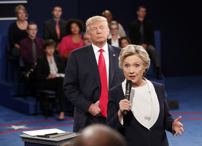 Donald Trump stands behind Hillary Clinton as she speaks during the second presidential debate in St. Louis on Oct. 9, 2016.