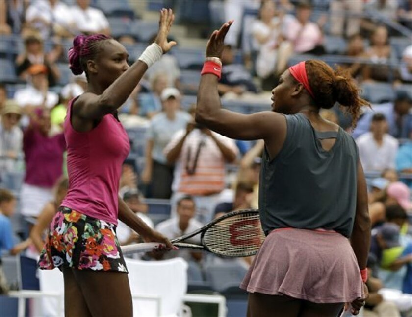 Venus, left, and Serena Williams high five after beating Raquel Kops-Jones and Abigail Spears in a doubles match during the second round of the 2013 U.S. Open tennis tournament, Saturday, Aug. 31, 2013, in New York. (AP Photo/Mike Groll)