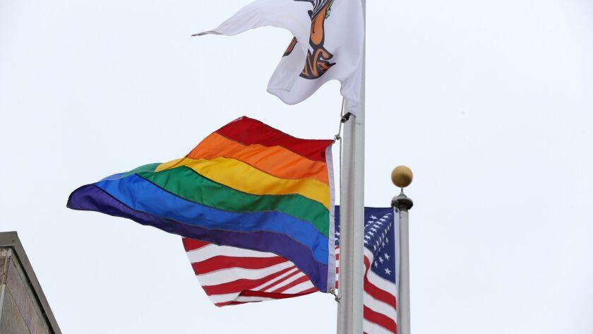 An LGBTQ rainbow flag flies