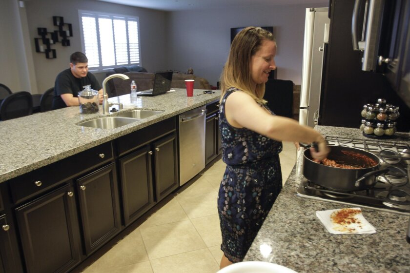 Jennifer Kelly cooks dinner as her husband Patrick sits nearby while in their new home in Murrieta on Tuesday.