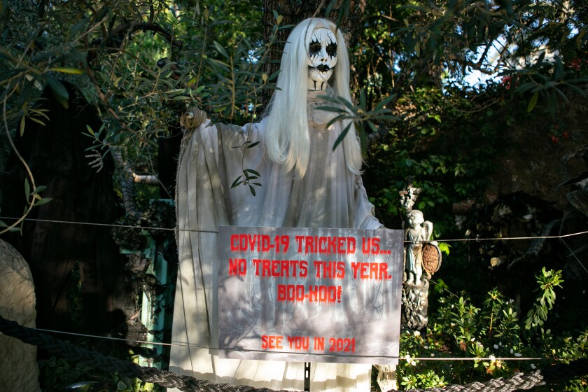 """A sign under a ghost decoration says """"COVID-19 tricked us. No treats this year. Boo-hoo! See you in 2021"""""""