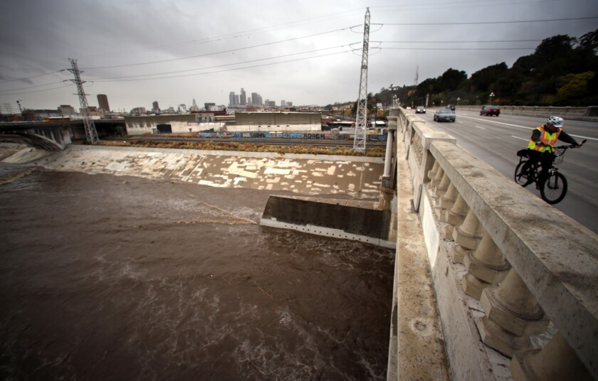 A man rides his bike across the Buena Vista Street Bridge as a swollen Los Angeles River flows below in Lincoln Heights in January. County officials are looking into ways to fund projects to capture more stormwater.