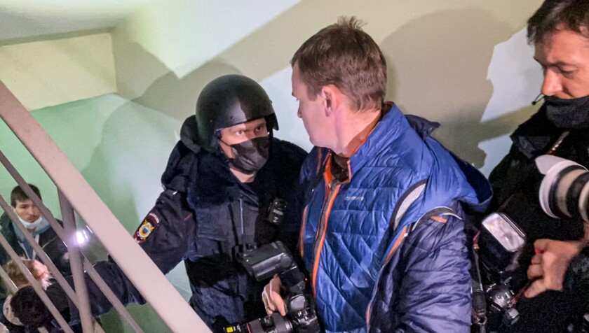 On a stairwell, a helmeted police officer confronts men with cameras.