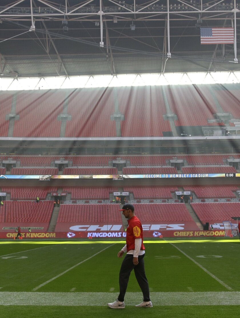 Sunlight filters through to Kansas City Chiefs quarterback Alex Smith (11) who walks on the pitch as he warms-up ahead of the NFL football game between Detroit Lions and Kansas City Chiefs Wembley Stadium in London,  Sunday, Nov. 1, 2015. (AP Photo/Matt Dunham)
