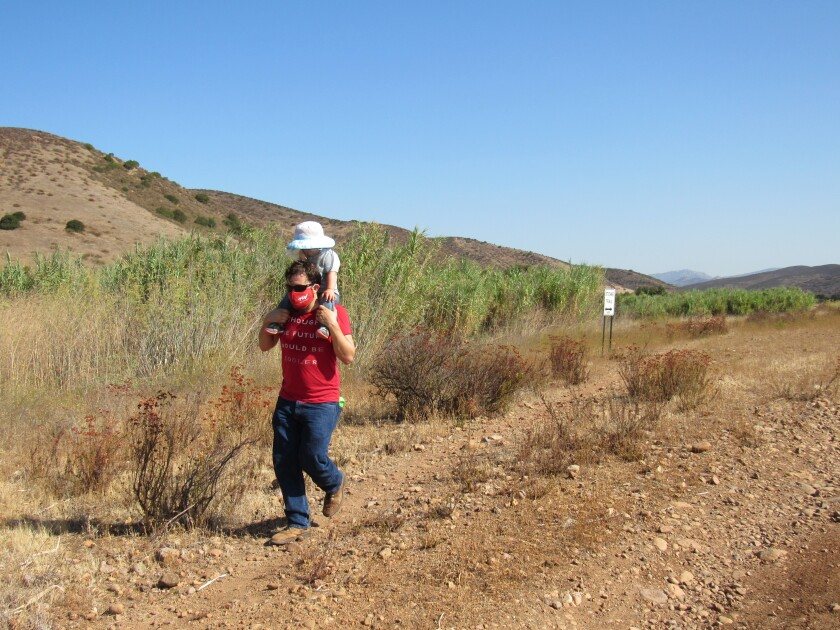 A hiker carries his child along part of the Stowe Trail earlier this year near planned homes on Fanita Ranch in Santee.