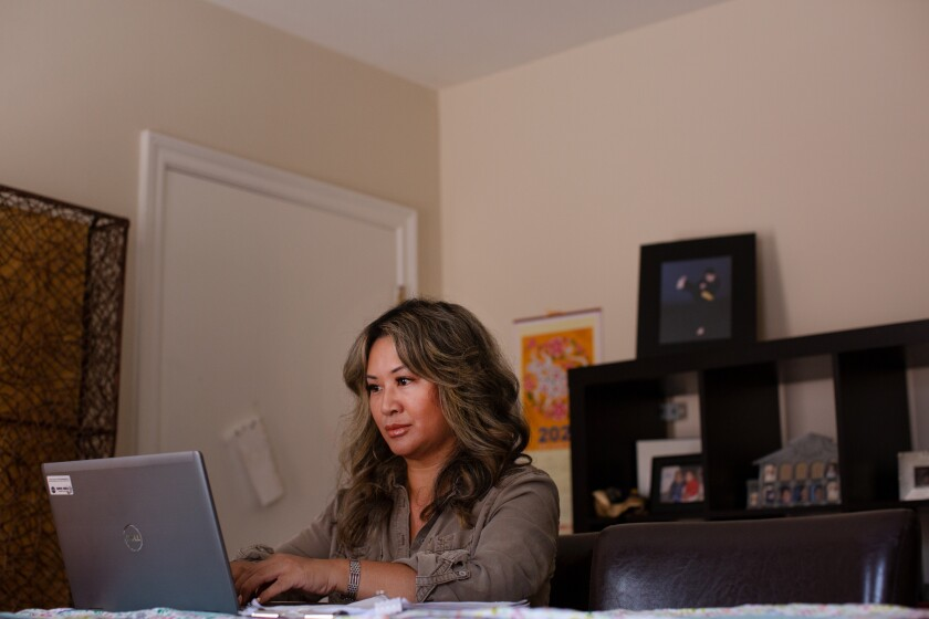 A woman types on a laptop in her home