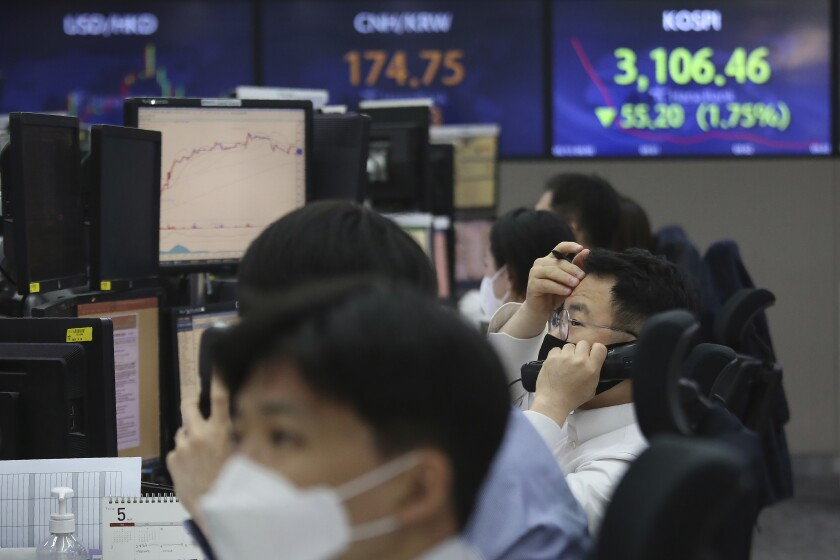 A currency trader talks on the phone at the foreign exchange dealing room of the KEB Hana Bank headquarters in Seoul, South Korea, Thursday, May 13, 2021. Asian stock markets followed Wall Street lower for a second day Thursday after unexpectedly strong U.S. consumer price rises fueled worries inflation might drag on an economic recovery. (AP Photo/Ahn Young-joon)