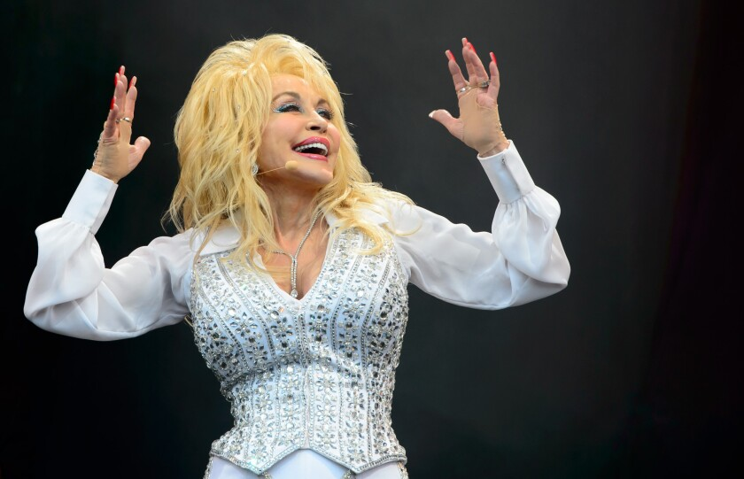 """Dolly Parton performs at the Glastonbury Festival in England last June. On Friday, NBC announced that it had signed a deal to develop a slate of TV movies """"based on the songs, stories and inspiring life"""" of the country music legend."""