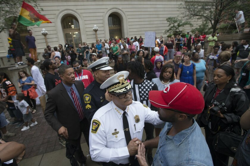 Cincinnati Police Chief Jeffrey Blackwell, center, shakes hands with a protestor during a demonstration outside the Hamilton County Courthouse after murder and manslaughter charges against University of Cincinnati police officer Ray Tensing were announced for the traffic stop shooting death of motorist Samuel DuBose, Wednesday, July 29, 2015, in Cincinnati. Hamilton County sheriff's spokesman Michael Robison says 25-year-old Tensing turned himself in at the county justice center Wednesday afternoon. (AP Photo/John Minchillo)