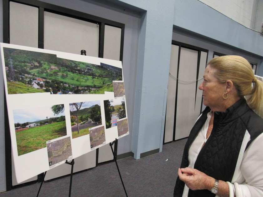 Deborah Hafer of El Cajon looks over proposed plans for Cottonwood Golf Club at a meeting on Nov. 4 at Hillsdale Middle School in Rancho San Diego. Hafer, a regular golfer on the course, is part of a contingent concerned about the owner's plans to turn the Cottonwood grounds into a sand mining operation.