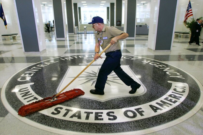 The lobby of the CIA, where an employee sweeps the CIA logo on the floor with a broom.